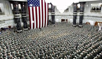 US soldiers from various branches of the military stand at attention during a mass reenlistment ceremony at the Al-Faw Palace, one of former Iraqi president Saddam Hussein's main palaces, in Baghdad on July 4, 2008. More than 1,200 US service members took a reenlisment oath on the 4th of July, the anniversary of US independence, led by top commander in Iraq General David Petraeus. (ALI AL-SAADI/AFP/Getty Images)