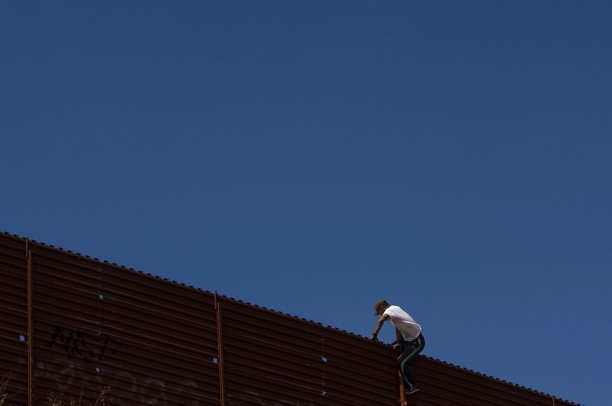 After peering into the U.S. from atop the U.S.-Mexico border fence, a man returns to the Mexican side in Tijuana, Mexico. But Indian tribes are calling for a halt to building the fence, arguing it will destroy their traditions and religious practices. (Associated Press)