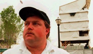 Security guard Richard Jewell poses on Sunday, July 28, 1996, across from the tower where he found a bomb and warned visitors at Centennial Olympic Park early Saturday morning. The Atlanta Journal-Constitution had named Jewell as a suspect in the bombing. (AP Photo/Atlanta Journal-Constitution, William Berr) ** FILE **