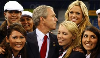 President Bush poses for photos with the U.S. women's softball team, including Jennie Finch, back row right, as he greets members of the U.S. Olympic team prior to the opening ceremony for the 2008 Olympics in Beijing, Friday, Aug. 8, 2008. (AP Photo/Gerald Herbert)
