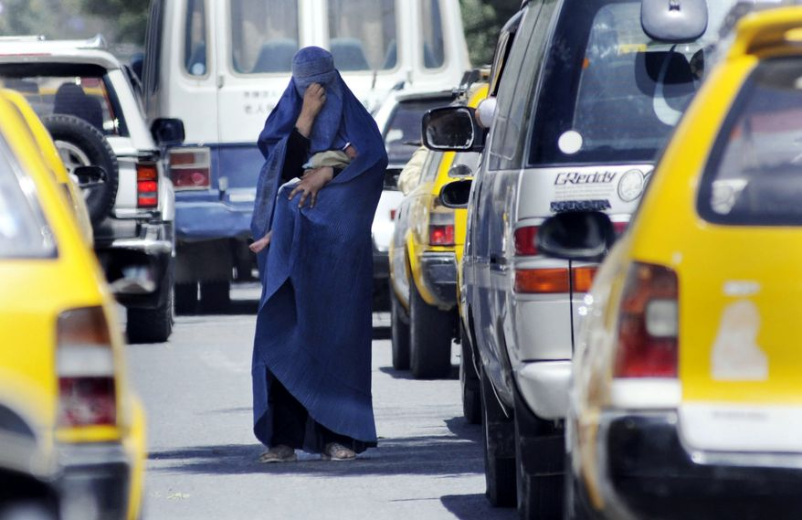 ** FILE ** A woman in a burqa begs for money with her baby tucked in her arms in central Kabul, Afghanistan. (The Washington Times)