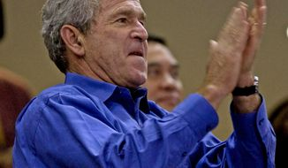 U.S. President George W. Bush whistles while watching a USA and China compete in a preliminary round of the men's Olympic basketball competition in Beijing on August 10, 2008.  USA won 101-70.  (UPI Photo/Stephen Shaver)