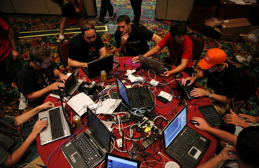 """** FILE ** In this 2008 file photo, participants compete in the """"Capture the Flag"""" hacking competition, a highlight of the DefCon conference in Las Vegas. After qualifying before the conference, teams battle to seize and keep control of a network set up for the game. (Associated Press)"""