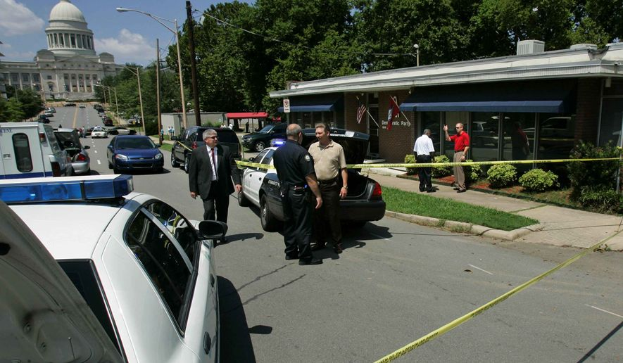 Police gather in front of the Democratic Party of Arkansas headquarters, right, near the Arkansas state Capitol in Little Rock, Ark., after responding to reports of shots being fired inside the building Wednesday, Aug. 13, 2008. Police said a gunman shot party chairman Bill Gwatney, who was critically injured. (AP Photo/Danny Johnston)
