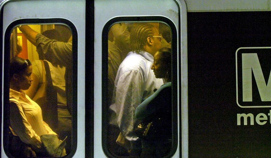 **FILE** Rush-hour commuters ride a Metrorail train in the District. (Associated Press)