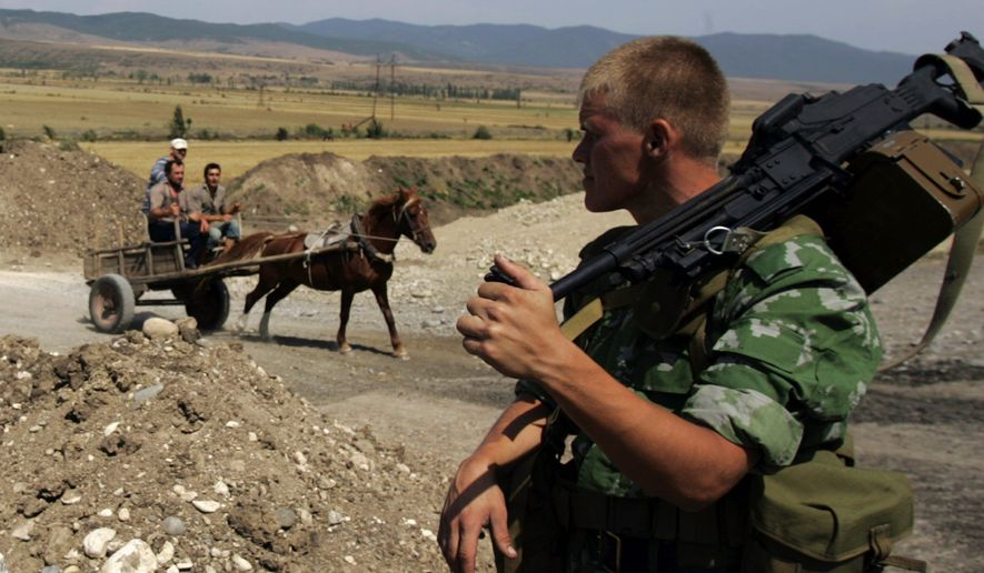 A horse driven cart moves past a Russian soldier at a checkpoint in Khurvaleti, near Gori, Georgia, Monday, Aug. 18, 2008. Russian troops and tanks control a wide swath of Georgia, including the country's main east-west highway. Russian President Dmitry Medvedev has promised the withdrawal under terms of an EU-backed cease-fire agreement, but how quickly the troops will leave is unclear, as is exactly where they will redeploy. (AP Photo/Darko Bandic)
