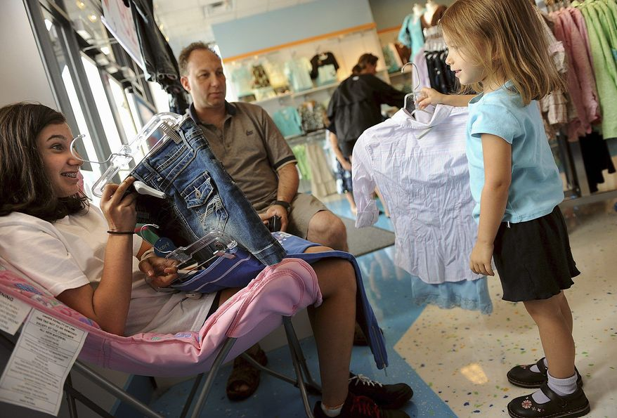 **FILE** Rebecca Peltz, 12, receives fashion advice from her sister Macy, 4, as their father, Andy, looks on at the Justice Just for Girls store in Sterling, Va., on August 24, 2008. The family, from Ashburn, Va., was shopping for back-to-school clothes. (The Washington Times)