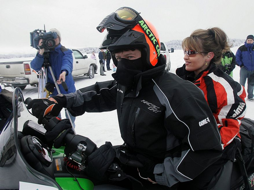 ** FILE ** Todd Palin (center) drives his wife, Alaska Gov. Sarah Palin, to the starting line of the Iron Dog snowmobile race in Big Lake, Alaska, on Feb. 11, 2007. (AP Photo/Al Grillo)