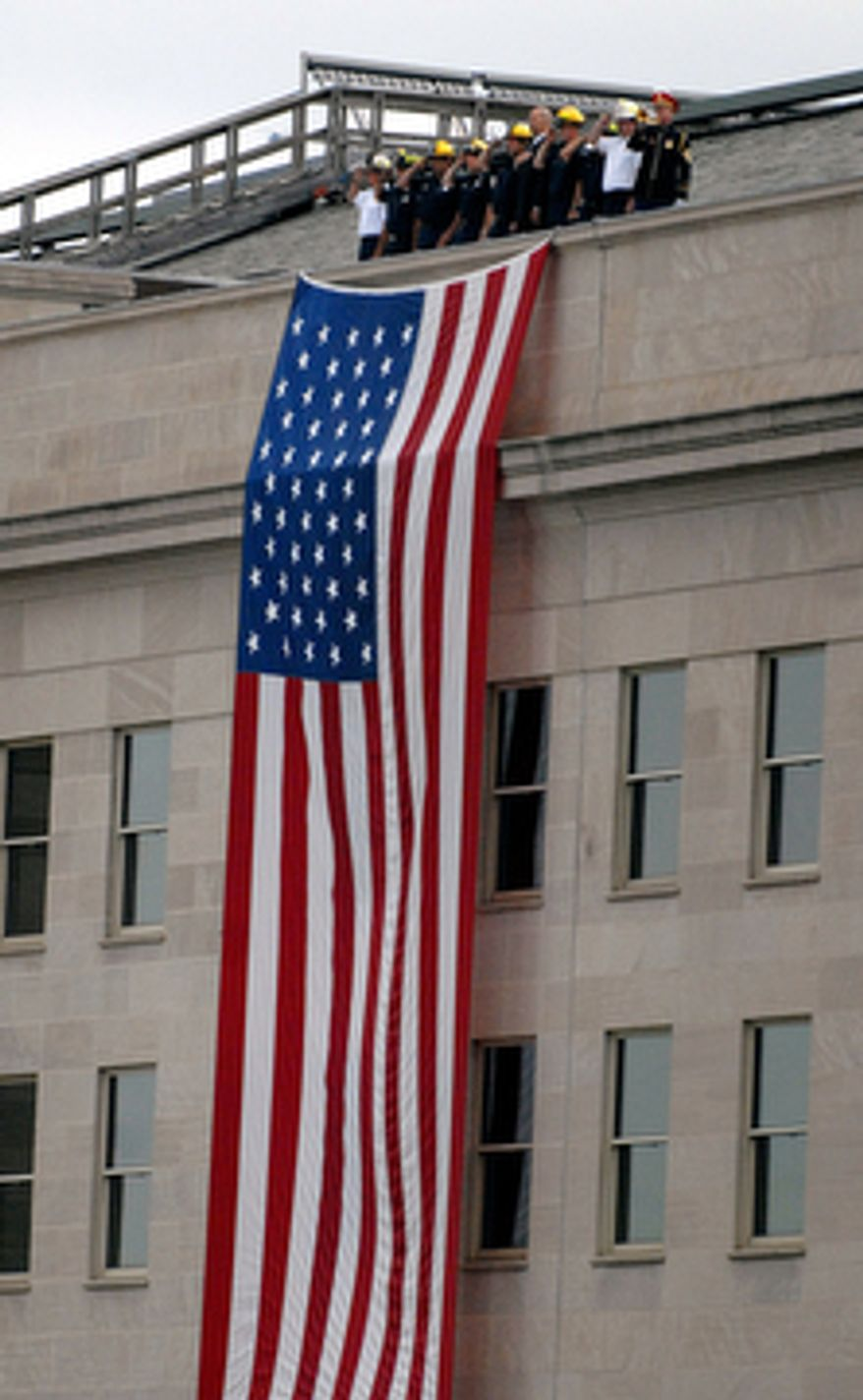 First responders stand attention next to the U.S. flag during the Pentagon Memorial Dedication ceremony remembering the 184 victims killed during the September 11 terrorist attacks in 2001 outside the Pentagon in Pentagon City, Va.(Astrid Riecken/The Washington Times)