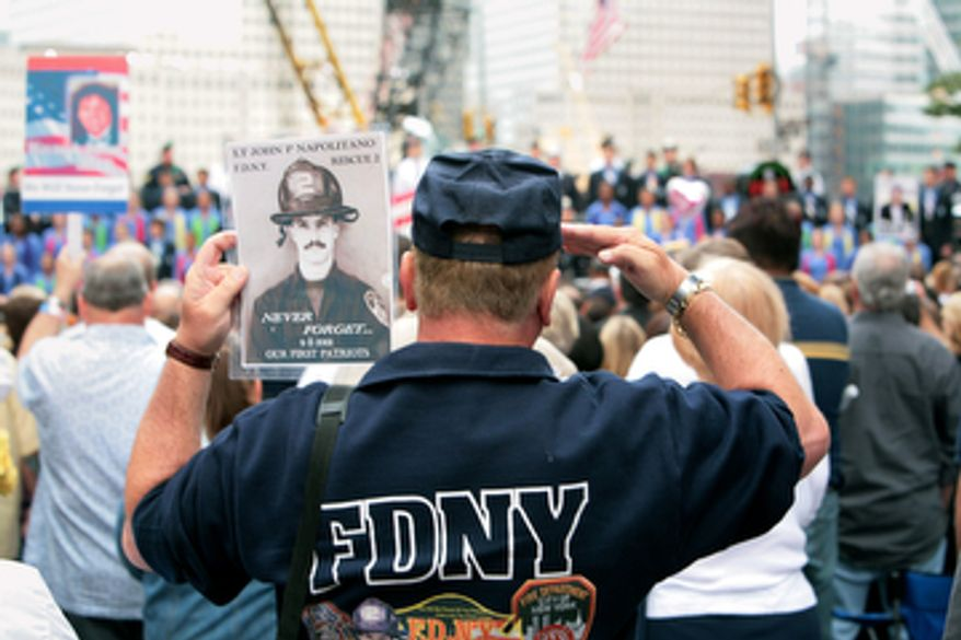 A fireman, holding the photo of 9/11 victim Lt. John P. Napolitano, FDNY, salutes near Ground Zero during the ceremony marking the seventh anniversary of the 9/11 terrorist attacks on the World Trade Center in New York on September 11, 2008.    (UPI Photo/James Estrin/POOL)