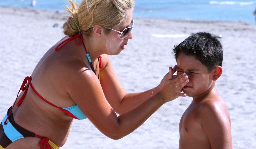 BLOOMBERG NEWS Darly Ortega of New York applies sunscreen on her son, Sabatian.