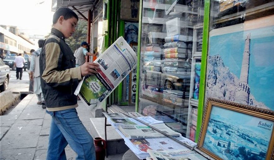 A young Afghan reads an English-language newspaper outside bookshop in Kabul. Researchers note that humanitarian crises occur most often in places where people don't speak English and that a lack of knowledge of foreign languages can affect national security. (Associated Press/File)