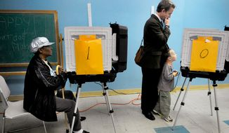 l-r, Helen Talley, 73, votes, while five year old Sean Leonard gets a civics lesson watching his dad Ken Leonard, 41, vote. (Mary F. Calvert / The Washington Times)