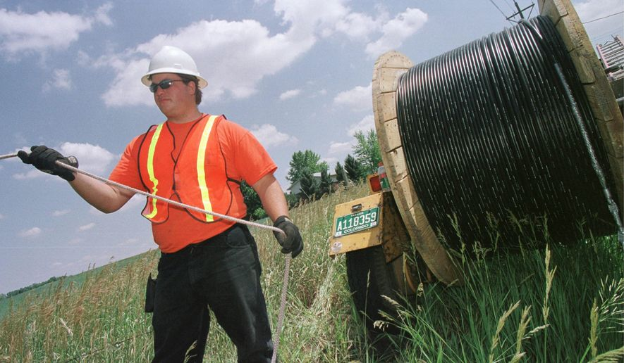 Reel tender Mo Laussie watches fiber-optic cable as he helps install the cable onto telephone poles in 2001 in Louisville, Colo.
