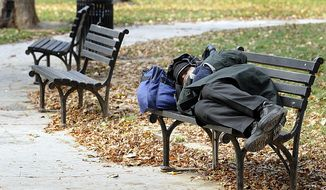 A homeless man sleeps on a bench in the park across the street from the Franklin School shelter, in Washington, D.C. (Barbara L. Salisbury/The Washington Times) ** FILE **