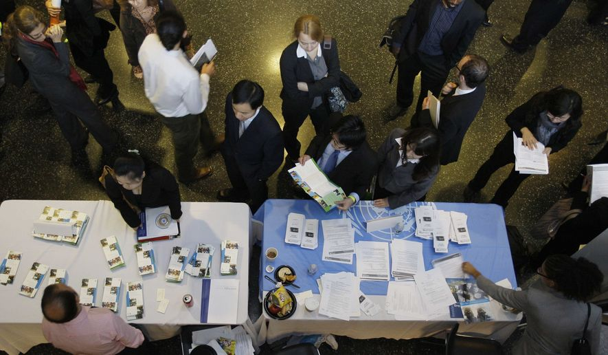 Columbia University students line up to speak with Roberto Amorosino, bottom left, of the World Bank about possible employment opportunities during a career fair at the school Friday, Nov. 7, 2008, in New York. (Associated Press) ** FILE **