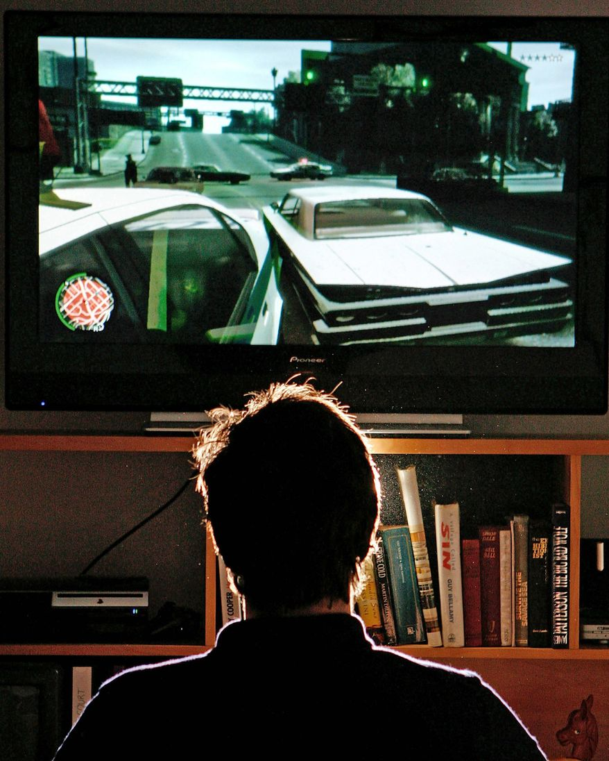 **FILE** A man plays Grand Theft Auto IV on the game's day of release April 29 in London. The video game was in high demand and sold out in stores. (Getty Images)