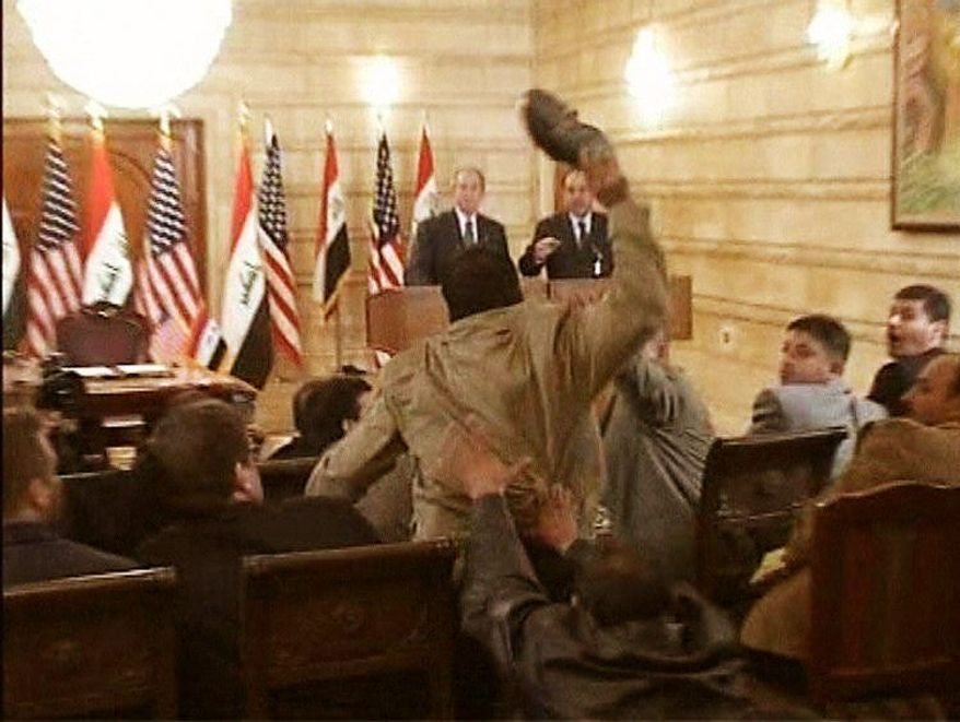 In this image from APTN video, a man, center, throws a shoe at U.S. President George W. Bush, background left, during a news conference with Iraq Prime Minister Nouri al-Maliki, Sunday, Dec. 14, 2008, in Baghdad, Iraq. On an Iraq trip shrouded in secrecy and marred by dissent, Bush on Sunday hailed progress in the war that defines his presidency and got a size-10 reminder of his unpopularity when a man hurled two shoes at him during a news conference. (AP Photo) ** FILE **