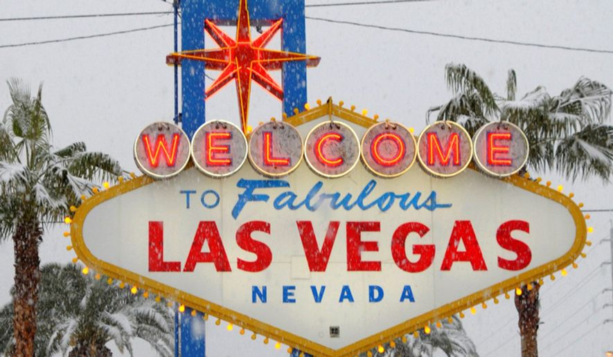 People play in the snow in front of the Las Vegas welcome sign in Las Vegas on Wednesday, Dec. 17, 2008.  (AP Photo/Las Vegas News Bureau, Darrin Bush)