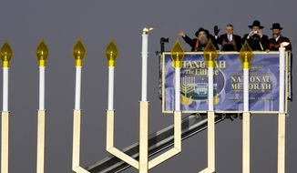 White House Chief of Staff Joshua B. Bolten second from left, Rabbis Abraham Shemtov, left, Levi Shemtov and Nachman Holtzberg, right, light the National Hanukkah Menorah, at the Ellipse, near the White House during a lighting ceremony marking the beginning of the celebration of the Hanukkah, Sunday Dec.. 21, 2008. Associated Press.