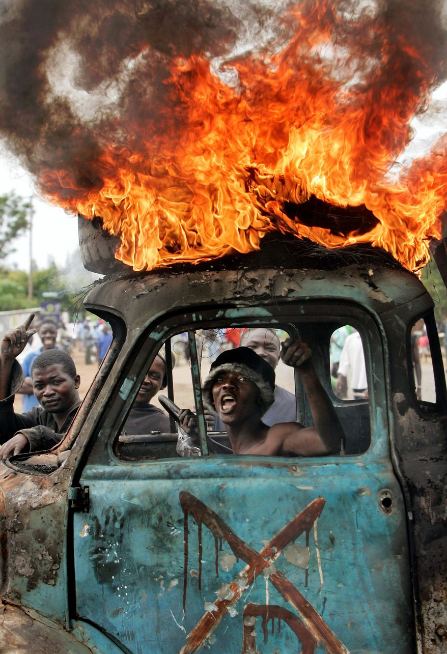 **FILE** A Kenyan man sits in a destroyed truck used as a makeshift roadblock while a tire burns on the vehicle's roof in Kisumu, Kenya, in late January 2008, a month of violence after disputed elections. (Associated Press)