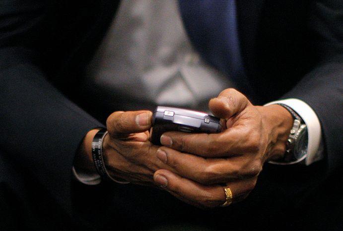 ** FILE ** Then President-elect Barack Obama checks his BlackBerry in St. Louis.