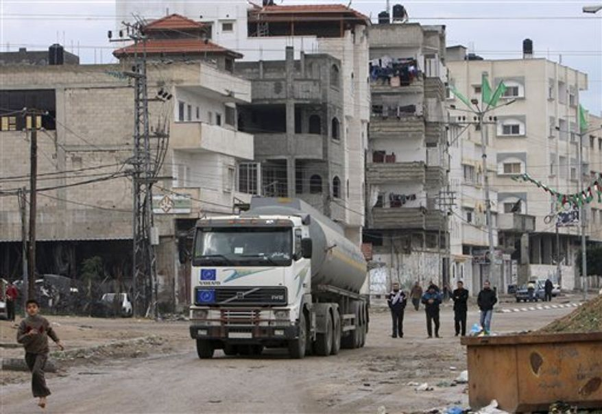 ** FILE ** A Palestinian child runs in front of a fuel truck as it drives near the Karni crossing, southeast of Gaza City on the border between Israel and the Gaza Strip, on Friday, Dec. 26, 2008. (AP Photo/Adel Hana)