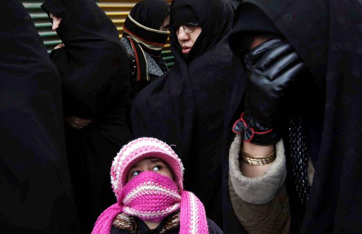 An Iranian girl and women react as they attend a religious procession to mark Ashura in Ardebil, Iran, in 2009.  (AP Photo/Hasan Sarbakhshian)
