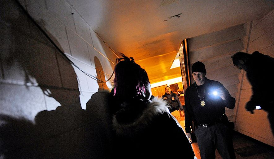 ATF Special Agent Brian Swann shines a flashlight on a couple of suspects in the Creighton Apartments during a routine patrol of the Violence Crime Impact Team (VCIT) in Richmond on Thursday, Dec. 4, 2008. (Barbara L. Salisbury / The Washington Times)