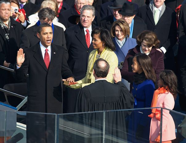 ** FILE ** Barack Obama takes the oath of office, becoming the 44th president of the United States and the first black person to hold the position on Jan. 20, 2009. He is joined on the Capitol steps by wife Michelle and daughters Malia (second from right) and Sasha. He was sworn in using the Bible from Abraham Lincoln's first inauguration, in 1861. (J.M. Eddins Jr./The Washington Times)