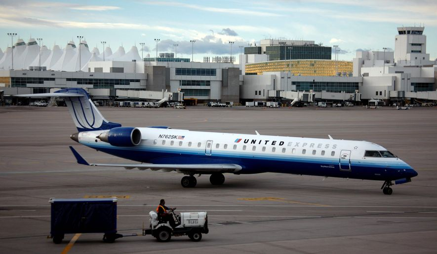 Associated press photographs A United Express jetliner backs away from a gate at Denver International Airport. Its parent, UAL Corp., Wednesday reported it had lost $1.3 billion in the fourth quarter because of operating losses and fuel-price bets that turned sour as oil prices fell.