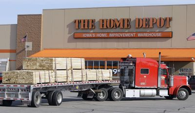 **FILE** A semi hauling a load of lumber pulls through the Home Depot store parking lot in Ankeny, Iowa, on Nov. 18, 2008. (Associated Press)