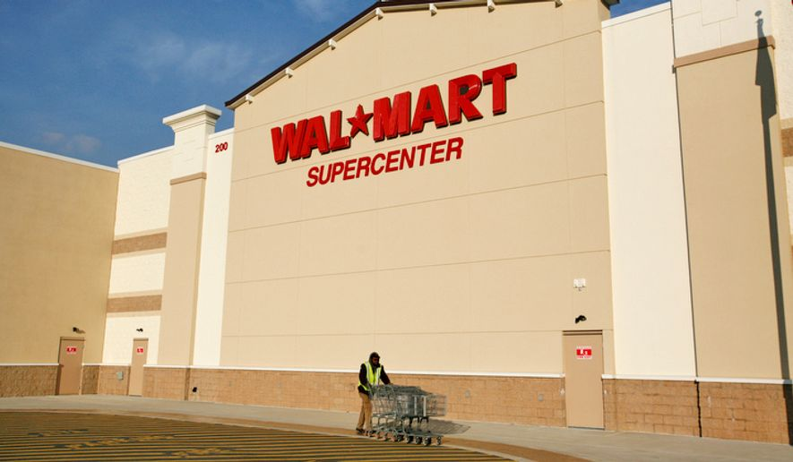 ** FILE ** An employee collects carts outside a Walmart Supercenter in Kilmarnock, Va., on January 13, 2009. (The Washington Times)