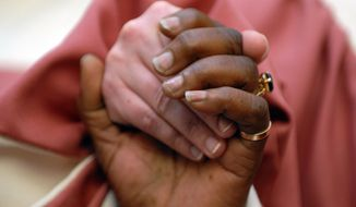 Members of the Bethel Apostolic Church Ensemble in Maryland hold hands during a prayer breakfast in 2009. (Astrid Riecken/The Washington Times/File)