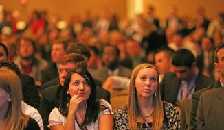 Katie Falkenberg/The Washington Times Two young women listen attentively to a speaker Thursday at the three-day Conservative Political Action Conference in Washington.
