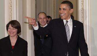 President Barack Obama, accompanied by Sen. Amy Klobuchar, D-Minn., arrives on Capitol Hill in Washington, Wednesday, March 25, 2009, to meet with senators to discuss his budget. (AP Photo/J. Scott Applewhite)