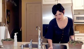 """This 2009 file photo shows a stay-at-home mom who reduces costs by doing housework herself. A Norwegian study published in August 2019 suggests that doing an hour's worth of light housework each day could help stave off an early death. """"Doing something is better than doing nothing,"""" a co-author of the study said regarding daily physical activity. (Associated Press) **FILE**"""