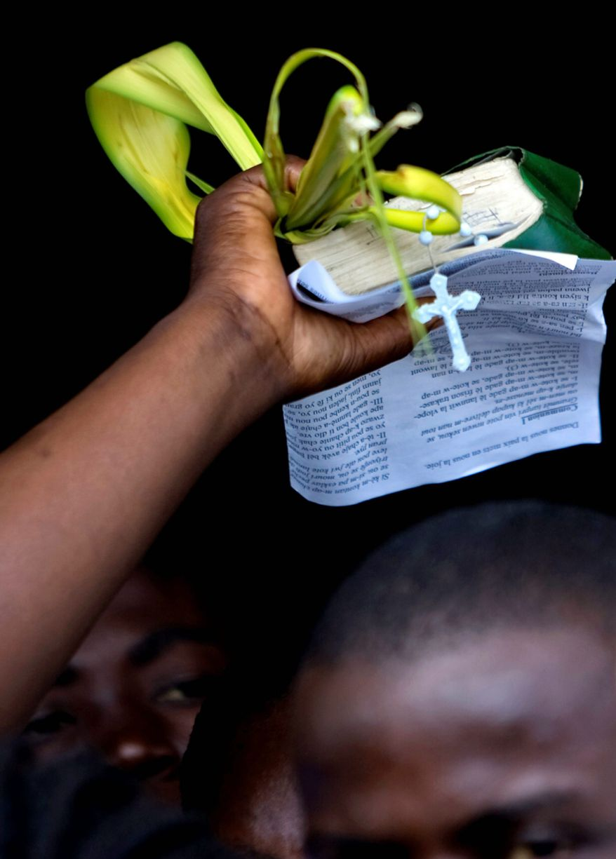 A woman holds palm fronds and a Bible during Palm Sunday celebrations in Port-au-Prince, Haiti.  