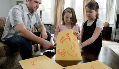In this 2009 photo, Kevin McLaughlin's then-8-year-old daughter Chloe (center) and her friend Caleigh Everitt, 9, count some of the allowance money Chloe keeps in different envelopes at the McLaughlin home in Pine Beach, N.J. One envelope is for spending, one for savings and one is for giving. (Associated Press)