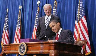 **FILE** President Obama signs the $787 billion economic stimulus bill in Denver in February 2009 as Vice President Joseph R. Biden Jr. looks on. (Associated Press)