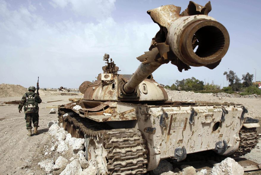 **FILE** An Iraqi soldier is seen near an Iraqi Army tank, which was destroyed in the U.S.-led invasion, in Basra, Iraq's second-largest city, 340 miles southeast of Baghdad, Iraq, on April 9. (Associated Press)