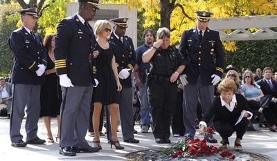 ** FILE ** Family members and friends of fallen Prince George's County police Sgt. Richard Findley place roses at the National Law Enforcement Memorial during the 17th Annual Wreath Laying Ceremony in Washington on Oct. 15, 2008. (UPI Photo/Kevin Dietsch)