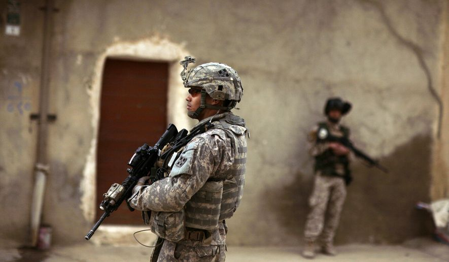 **FILE** - In this March 13, 2009 file photo, an Iraqi Army soldier and a U.S. Army soldiers from Delta Co., 1st Combined Arms Battalion, 67th Armor Regiment stand guard during a joint patrol in Mosul, 360 kilometers (225 miles) northwest of Baghdad, Iraq. The Feb. 24, 2009 shooting, which killed a U.S. solider and an interpreter and wounded five others, was an alarming inside job that reinforced what many fear: insurgents and sympathizers possibly infiltrating the ranks of Iraq's security forces. (AP Photo/Maya Alleruzzo, file)
