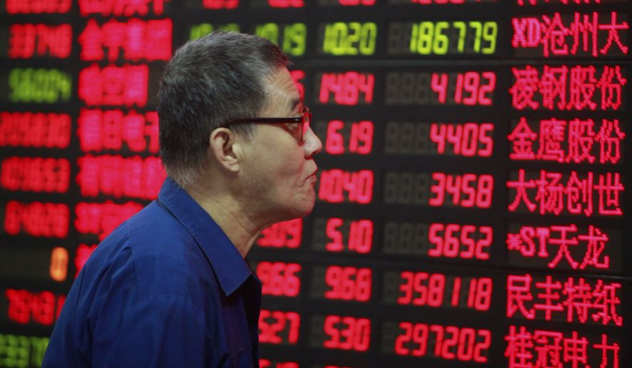 An investor looks at the stock price monitor at a private securities company in Shanghai. (AP Photo)