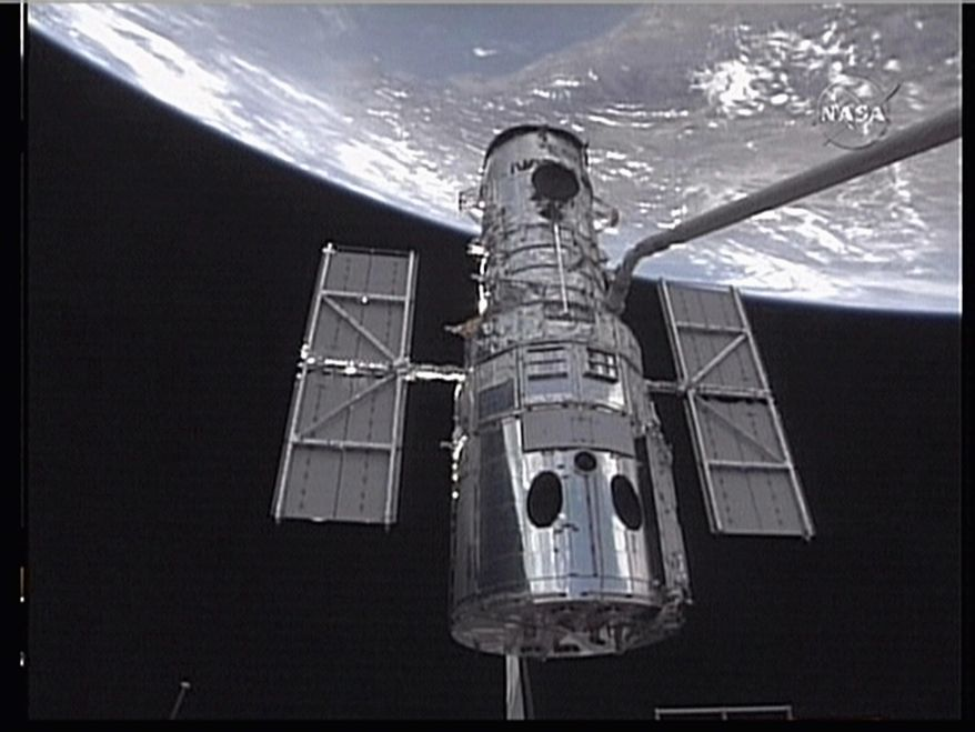 AGENCE FRANCE-PRESSE/GETTY IMAGES In this image taken from NASA video, the Hubble Space Telescope is captured by Space Shuttle Atlantis' robotic arm as astronauts start a mission to service the space telescope.