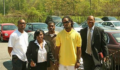 Mentor Debra Rowe escorts Jason Wren (center) into Providence St. John Baptist Church as part of a program to keep citizens on the right path after incarceration. They are accompanied (from left) by Reginald Hutchinson, Ms. Rowe's son, Alphonso Allen, and Andre Tillman. (James C. Allen)
