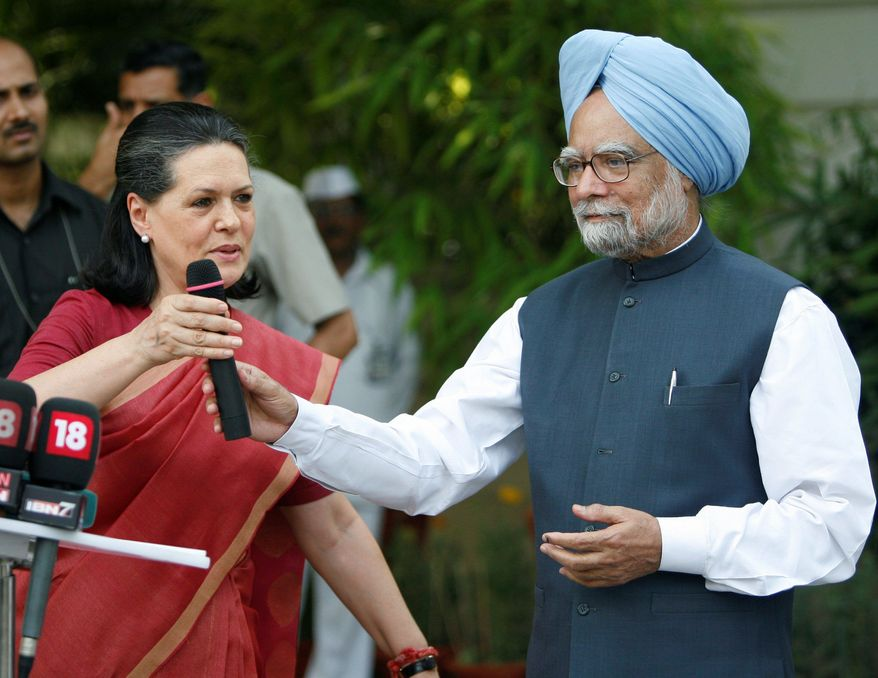 ** FILE ** Congress party President Sonia Gandhi (left) and Indian Prime Minister Manmohan Singh take turns addressing the media at her residence in New Delhi in 2009 after Mr. Singh declared victory in India's national elections. (Associated Press)