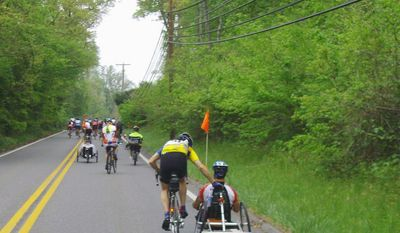 ** FILE ** Clint Provenza of Severna Park, Md., assists a participant up a hill during the Wounded Warrior Project Soldiers Ride in Annapolis. Below, eager riders line up at the starting line. (Tom Galligan/The Washington Times)