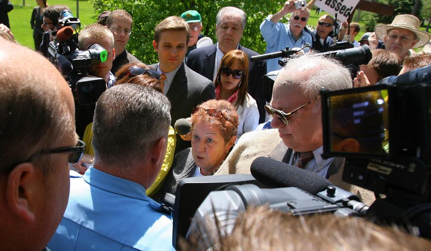 Norma McCorvey (bottom center) is confronted by police Sunday after marching on campus at the University of Notre Dame in South Bend, Ind. At least five anti-abortion activists, including McCorvey, were led away in handcuffs Sunday from campus, where President Barack Obama was also to receive an honorary degree. (Associated Press)