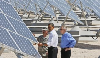 President Obama, accompanied by Senate Majority Leader Harry Reid (right), Nevada Democrat, and Col. Howard Belote, looks at solar panels at Nellis Air Force Base in Nevada on Wednesday, May 27, 2009. (AP Photo/Charles Dharapak)
